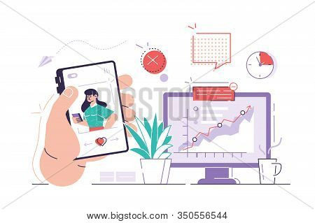 Worker Is Surfing Photos On His Phone On Social Media While Seated At His Desk Behind His Computer.