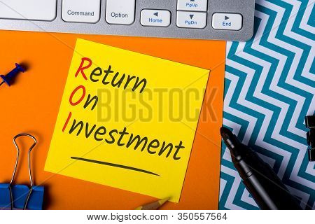 Roi Return On Investment Written On Dices In Message At Workplace Background. Business Performance I