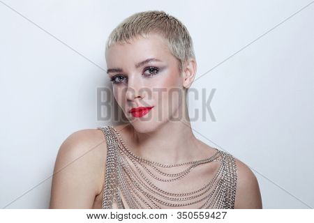 Vintage style portrait of young woman with short blonde hair and fancy makeup