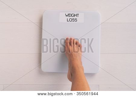 Weight loss woman stepping on scale weighting herself checking on challenge progress of life change diet healthy eating lifestyle. First person view in bathroom.