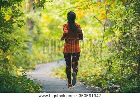 Run fit runner woman jogging in green spring forest woods park, healthy active lifestyle exercising cardio in nature outdoors. Girl running from behind.