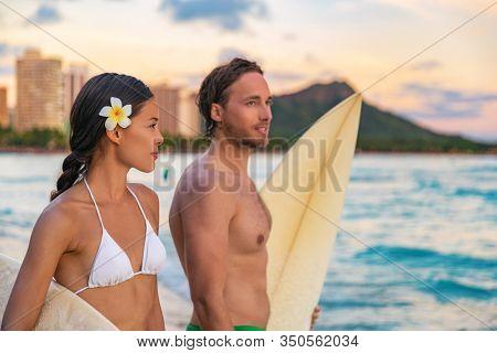 Hawaii beach couple tourists surfing on Waikiki beach, Honolulu, surf lesson summer travel vacation. Beautiful Asian bikini model woman, Caucasian man.