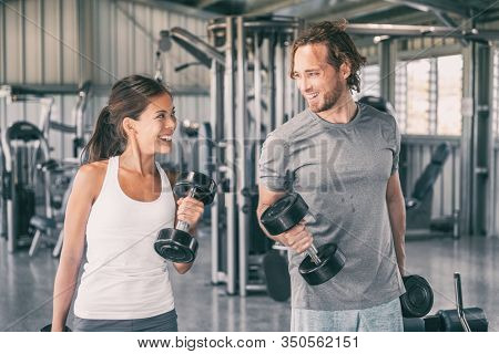 Fitness gym personal trainer coach training Asian woman with free weights dumbbell bicep curls workout talking having fun exercise partner. Fit man, happy girl.