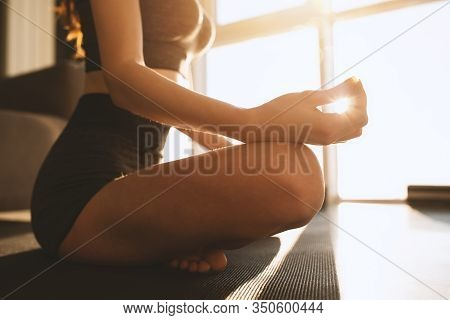 Young Girl Relaxing In Yoga Position In Front Of A Bright Window
