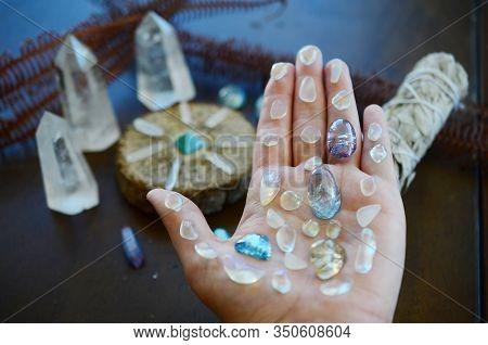 Tumbled healing crystals, shiny bright colors. Rainbow aura quartz, indigo aura quartz, champagne au