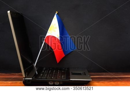 Flag Of Philippines , Computer, Laptop On Table And Dark Background