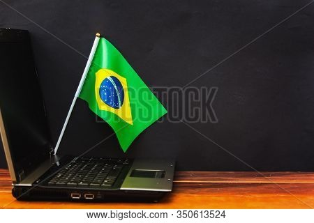 Flag Of Brazil , Computer, Laptop On Table And Dark Background