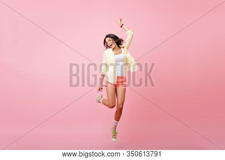 Full-length Portrait Of Slim Young Woman With Tanned Skin Jumping With Smile On Pink Background. Stu