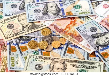 Various Coins Lying Over Different Currency Banknotes Dollars And Rubles Close Up. Money Background