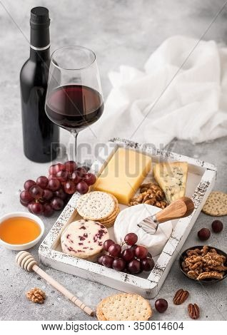 Glass And Bottle Of Red Wine With Selection Of Various Cheese In Wooden Box And Grapes On Light Back