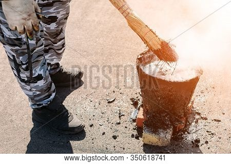 Worker Repairs The Roof With Molten Tar From A Bucket With A Broom. Roof Repair Tar. Poor Repair Of