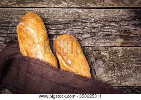 French Baguette Bread On Old Rustic Wooden Background. French Bread Baguettes, Top View, Copy Space.