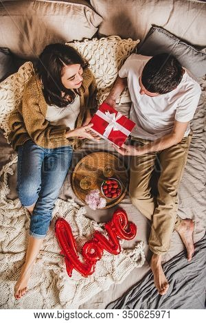 Young Happy Couple Sitting In Bed And Giving Presents