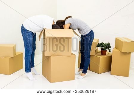 Wife And Husband Are Busy, Unpacking The Carton Boxes. They Are Standing Ducking Their Heads Into Th