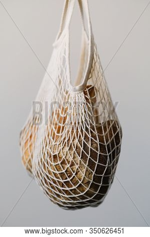 Different Buns Of Fresh Bread In Wicker String Bag On Gray Background. Freshly Baked Wheat Bread, St