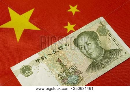 Chinese Yuan Against The Backdrop Of The Chinese Flag. One Yuan. Chinese Currency And Economy Concep
