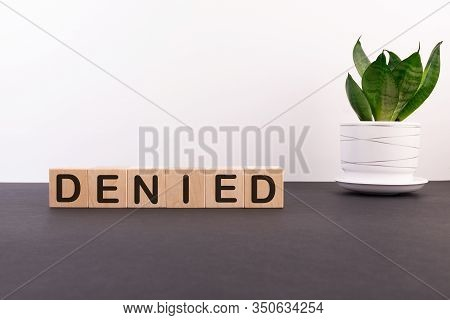 Denied Word On Wooden Cubes On A Dark Table With Flower And Light Background