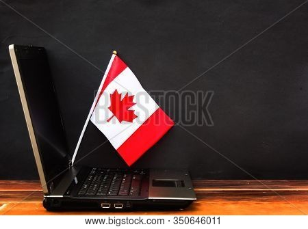 Flag Of Canada , Computer, Laptop On Table And Dark Background