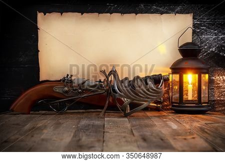 Vintage Horizontal Scroll With Place For Text On A Dark Wooden Wall Steel Epee Gun And Lantern With