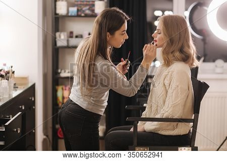 Makeup Artist Work In Beauty Studio. Woman Applying By Professional Make Up Master. Beautiful Make U