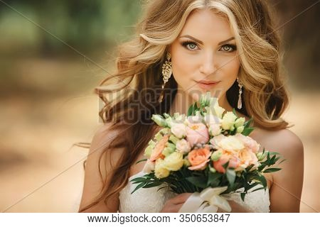 Portrait Of Beautiful Luxury Bride With Roses Wedding Bouquet Outdoors. Young Woman With Professiona