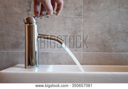 Faucet On The Washbasin In The Bathroom. The Person Opens Or Closes The Tap With Water