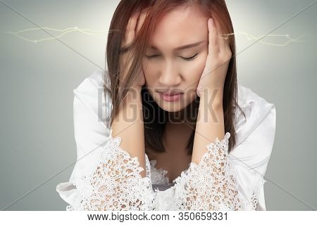 Asian Woman In Lace Nightgown And White Satin Robes Has A Headache, Isolated On Gray Background. Suf