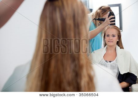 Mirror reflection of beautician drying long blond hair with hair dryer at parlor