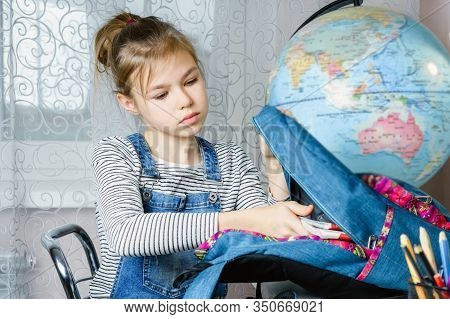 School Girl Packing Books In Backpack At The Table For School After Finishing Homework, Back To Scho