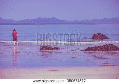 Woman Walking On Sandy Beach, Lofoten Norway