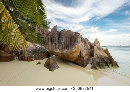 Tropical Beach At Curieuse Island Seychelles With Famous Volcanic Stones And Palm Tree Leafs. Nobody