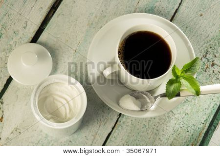 White stevia natural sweetener in powder form and a cup of coffee