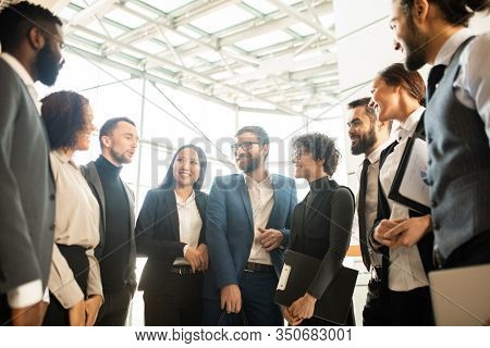 Group of creative young multi-ethnic business colleagues standing in circle and brainstorming about new campaign