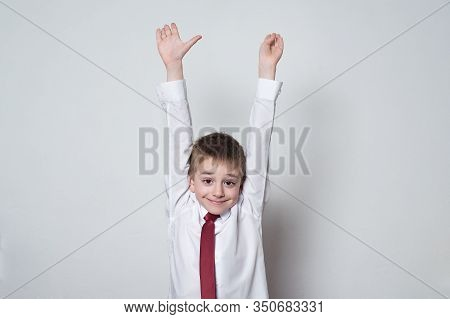 Little Boy In Shirt And Tie Raised His Hands Up. Middle School, Junior High School.