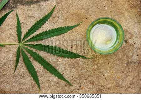 Green Marijuana Leaf Blurring, Hemp Oil In A Cup, Topview. Cannabis Oil, Flat Lay