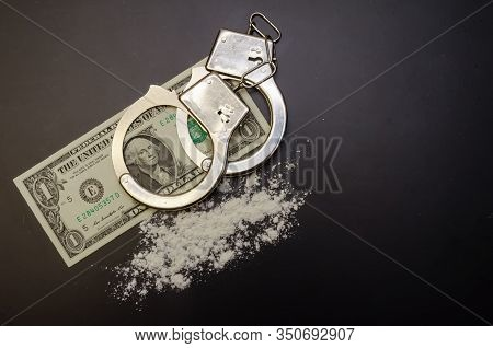 Handcuffs, Money And Cocaine Drugs On A Black Background Close-up With A Copy Space