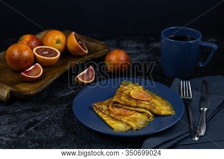 Two Crepe Suzette On A Classic Blue Plate, Golden Toasted With Slices Of Red Orange And In Syrup, A