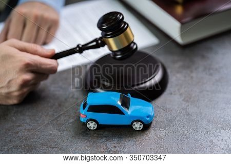 Close-up Of A Small Red Car In Front Of Judge Holding Mallet