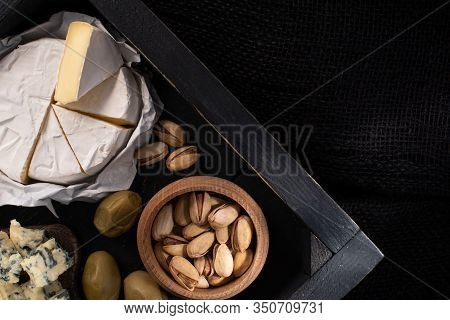 Top View Of Tray With Pieces Of Camembert And Dorblu, Dried Olives And Pistachios Isolated On Black