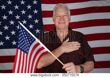 American Man Solutes the American Flag and repeats the Pledge of Allegiance. American Flag. Proud American. United States of America.