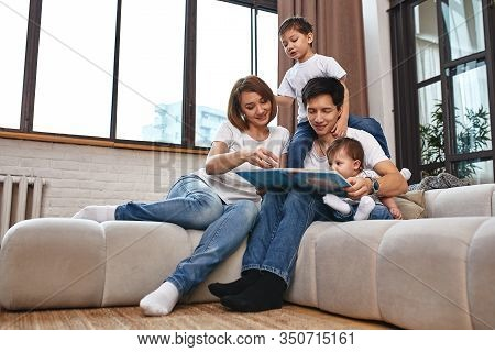 Happy International Family Concept. Dad, Mom, Son And Little Daughter Posing For A Camera At Home, A