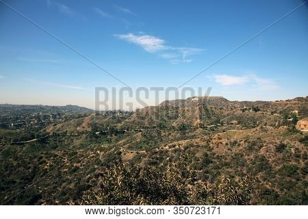 Hollywood, California / USA - 2/12/2020: View of Hollywood Hills and Hollywood Sign with, palm trees, and buildings. Tinseltown is known world wide for its Movies. Come to Hollywood and Be a Star.