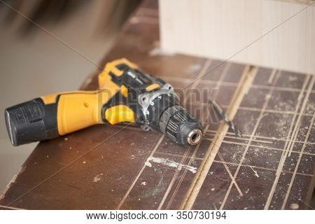Drill with wooden board in workshop, close-up