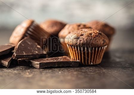 Tasty chocolate muffins. Sweet cupcakes and chocolate on old kitchen table.