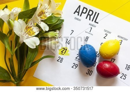 April 2020 Monthly Calendar With Three Colorful Easter Eggs And Spring Flowers On The Bright Yellow
