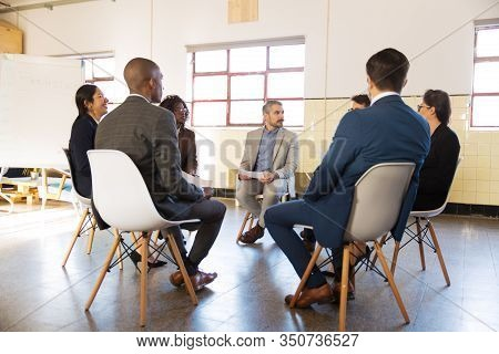 Focused Managers Sitting In Chairs With Paper Documents. Confident Office Employees During Meeting.