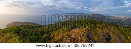 Aerial panorama of the island of Phuket during sunset. Area of the Black Rock viewpoint (the viewpoint itself is an area with dry yellow grass on the foreground). Thailand