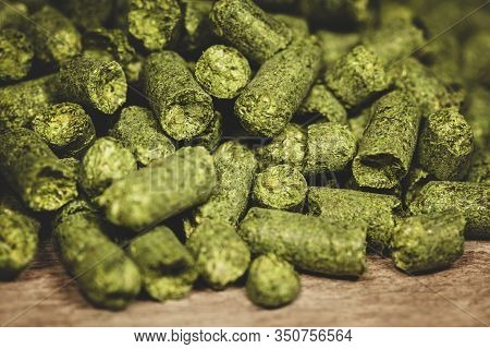 Dried Green Hop Pellets On Wooden Ground, Ingredient For A Brewery, Beer Plant Or Company, Closeup