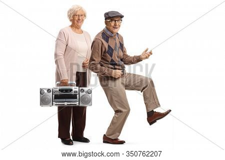 Full length portrait of an elderly woman with a boombox and a senior man dancing and pretending to play a guitar isolated on white background
