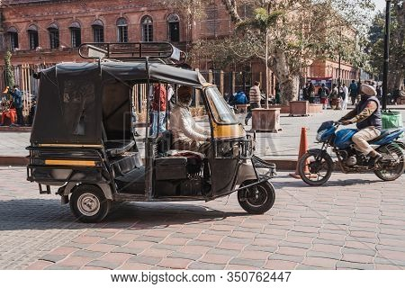Amritsar, India - Febuary 8, 2020: Tuk Tuk Driver (or Auto Rickshaw) In The Town Square Of Amritsar